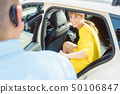 Taxi driver helping woman passenger out of the car 50106847