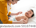 Young mother raising her baby 50107448