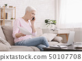 Upset senior woman talking on phone and working at home 50107708