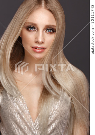 Beautiful blond girl in move with a perfectly smooth hair, and classic make-up. Beauty face. 50111748