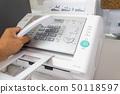 Hand man are using a fax machine send paper 50118597