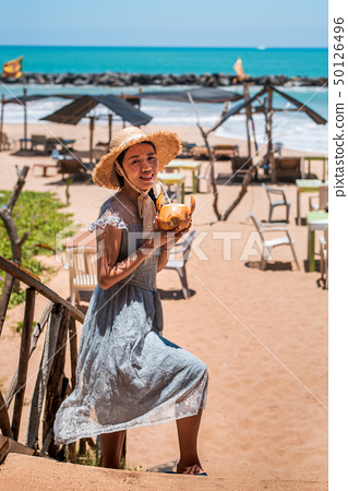 Woman with coconut on a tropical beach 50126496