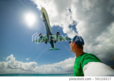 Slim girl on the beach wearing swimsuit with huge airplane flying over her head on Maho beach 50128817