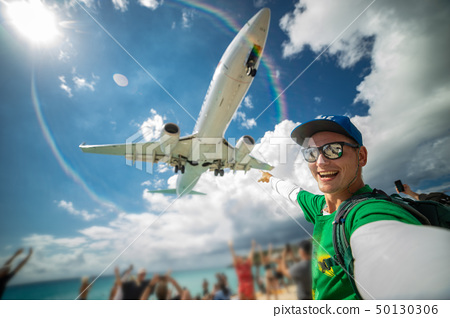 Smiling man taking selfie with airplane with beach, sea and lots tourists on background. Maho beach 50130306