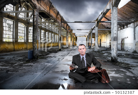 man sitting in a abandoned factory 50132387