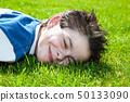 happy little boy lying on a lawn 50133090