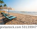 Sun umbrellas and chairs on tropical beach 50139947