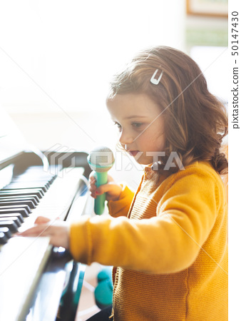 Girl toddler plays with piano and toy microphone. 50147430