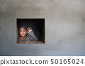 Asian girl looking out the window were imprisoned 50165024