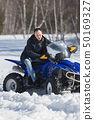 A winter forest in daylight. Cold weather. An adult man riding a big snowmobile 50169327