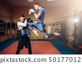 Male kickboxer doing kick in jump, kickboxing 50177012
