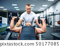 Athlete doing exercise under instructor control 50177085