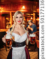 Sexy waitress holds two mugs of fresh beer in pub 50177136