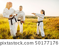 Master teaches karate fighters the correct stand 50177176