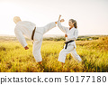 Male and female karate masters fight in field 50177180