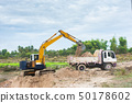 Yellow excavator machine loading soil into a dump 50178602