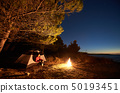 Woman having a rest at night camping near tourist tent, campfire on sea shore under starry sky 50193451