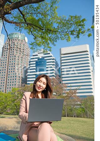 한국 여의도 빌딩가에서 노트북을 들고 일하는 비지니스 우먼 50195434