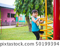 Active Asian Kid playing climbing metal spiral at 50199394