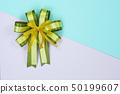 Decorative green ribbon bow on sweet pastel 50199607