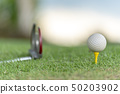 Golf ball on tee in golf field with recreation  50203902