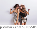 Two attractive girls, cheerful best friends dancing, having fun and drinking red wine on party 50205505