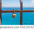 rusty padlock attached to a balustrade by the sea, 50219142