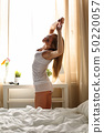 Beautiful smiling young long haired woman wake up early morning 50220057