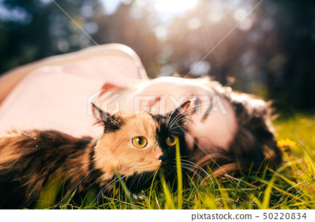 Girl lying on grass with cat. Spring or summer warm weather concept. Bokeh background. Ginger kitten 50220834