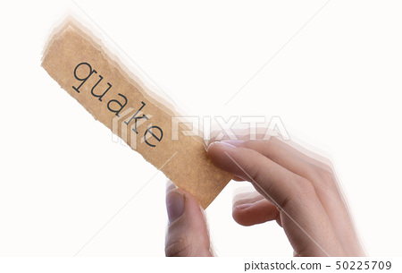Quake word on torn notepaper in hand 50225709