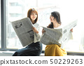 Two women reading a newspaper on the window side 50229263