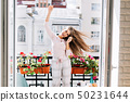 Portrait pretty young girl in pajamas having fun on balcony in city. She moves, raises hands. Her 50231644