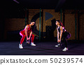 Two Attractive fit women athlete performing a kettle-bell swing in gym 50239574