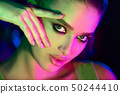 Girl with trendy make-up in colorful bright lights 50244410