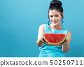 Young woman holding watermelon 50250711