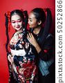 two pretty geisha girls friends: modern asian woman and traditional wearing kimono posing cheerful 50252866