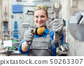 Woman mechanic showing tools to the camera 50263307