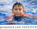 Happy asian kid boy swiming on swiming pool in the 50263558