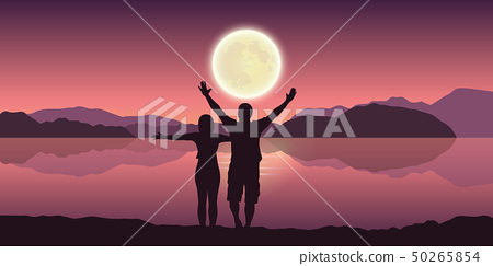 happy couple with arms raised enjoy the full moon and mountain landscape by the lake 50265854