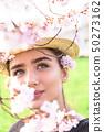 Girl in straw hat hid behind flowering branch 50273162