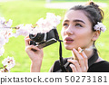 Girl holds camera and cigarette and looks up 50273181