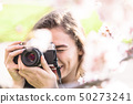 Young woman looks into camera lens and laughs 50273241