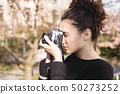 Girl with camera in hands taking pictures in park 50273252