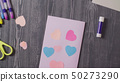 Greeting card and scissors on the table 50273290