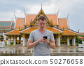Young tourist man using phone against view of the Buddhist temple in Bangkok 50276658
