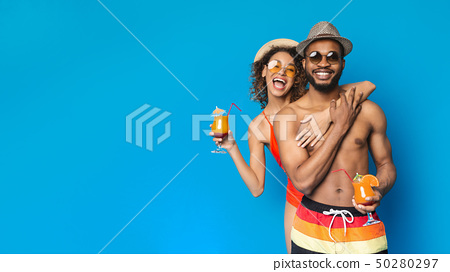 Cheerful black couple in sunglasses and hats drinking summer cocktails 50280297