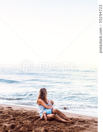 Young mother breasfeeding toddler daughter on beach on summer holiday. 50294722