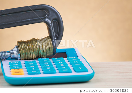 calculator and coins squeezed tightly in a G-Clamp 50302883