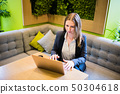 Young business woman working with laptop on the table in the city cafe interior 50304618