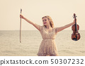 Woman on beach near sea holding violin 50307232